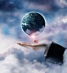 Plant Earth floating in clouds over businessman´s hand