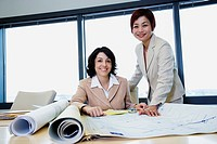 Portrait of two businesswomen with blueprints