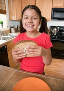 Hispanic girl eating sandwich in kitchen