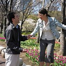 Asian couple laughing and holding hands in urban park