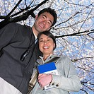 Low angle view of Asian couple with guide book