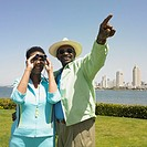 African couple using binoculars with cityscape in background