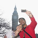 Asian couple talking own photograph with clock tower in London