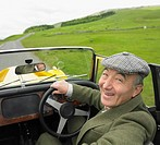 Senior Asian man driving old fashioned sports car in countryside (thumbnail)