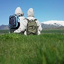 Rear view of couple wearing winter jackets looking at snow-capped mountains