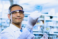 Indian male scientist smiling and holding DNA film