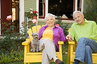 Senior couple sitting outdoors with dog
