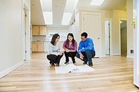 Asian couple looking at blueprints in new house