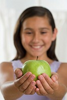 Hispanic girl holding apple in outstretched hands