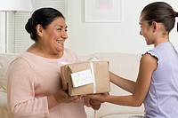 Hispanic girl giving gift to grandmother