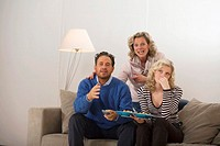 Parents with daughter sitting on sofa