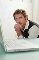 Young man sitting by laptop