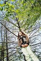 Low angle view of young girl under tree
