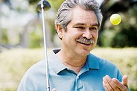 Middle-aged man with golf club and golf ball