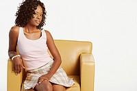Studio shot of African woman in armchair