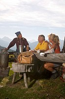 Couple at mountain hut, talking to peasant woman