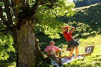 Couple having picnic under tree, woman dancing