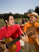 Hispanic father and adult son playing instruments at party