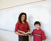 Female teacher with student in front of whiteboard