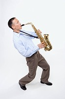 Studio shot of Asian man playing saxophone