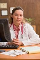 Hispanic female doctor at desk