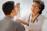Senior Hispanic female doctor examining patient