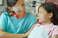 Indian female dental assistant smiling at young Asian female patient