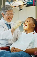 Senior Asian female dentist and African boy in dentist's chair (thumbnail)