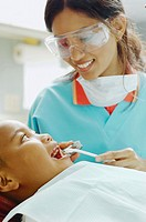 Indian female dental assistant working on African boy
