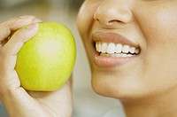 Close up of woman holding apple next to her mouth
