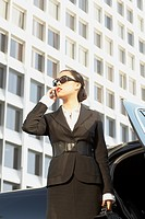 Asian businesswoman using cell phone next to car