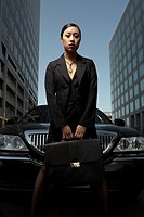 Asian businesswoman with briefcase next to car