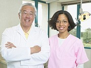 Senior Asian male dentist with African female dental assistant