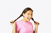 Studio shot of Hispanic girl holding her pigtails