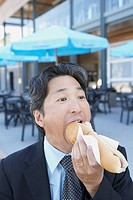 Asian businessman eating hot dog outdoors