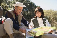 Senior couple looking at map near forest