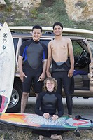 Portrait of multi-ethnic surfers next to truck