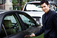 Portrait of a businessman unlocking a car door