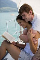 Young couple embracing on boat, woman reading book