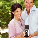 Portrait of a mature couple holding a camera