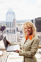 Portrait of a businesswoman holding a laptop with buildings in the background
