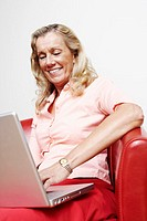 Close-up of a mature woman using a laptop and smiling