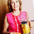 Portrait of a mature woman holding a jug of mango shake