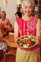 Portrait of a mature woman holding a bowl of salad and her friends sitting at the dining table in the background