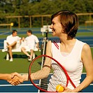Mid adult woman shaking hands with a woman on a tennis court