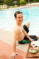 Portrait of a mature man sitting at the poolside