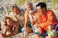 Two mature couples sitting on the beach and holding champagne flutes
