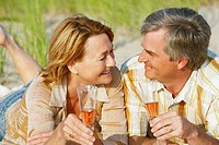Close-up of a mature couple lying on the beach and holding champagne flutes