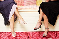 Low section view of two women sitting on the bed and wearing stilettos