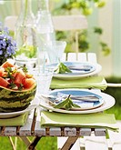 Laid table in garden with melon salad